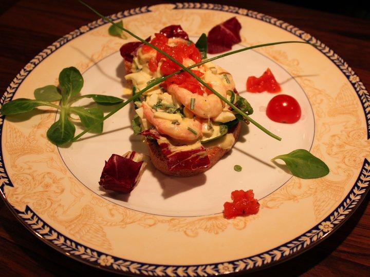 Hjemmelaget egg & rekesalat servert på ristet brød, med bakt tomatconcasse og salat av mâche og radicchio rosso.