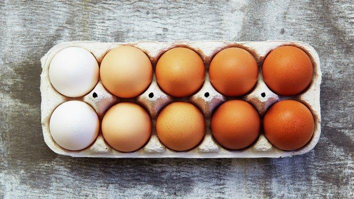 Hvite og brune egg i eggekartong