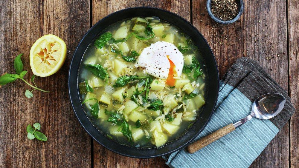 Grønn grønnsaksuppe med posjert egg og risoni