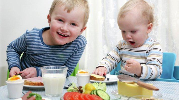 Magnus og Amund koser seg ved frokostbordet.