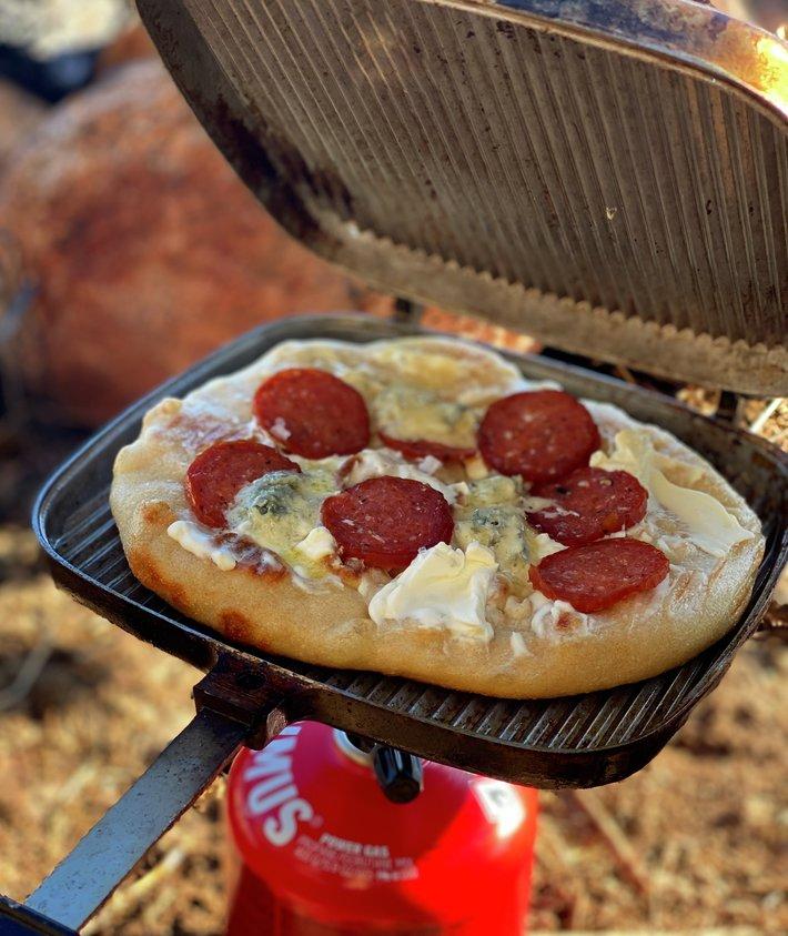 Hvit pizza med spekepølse på primus